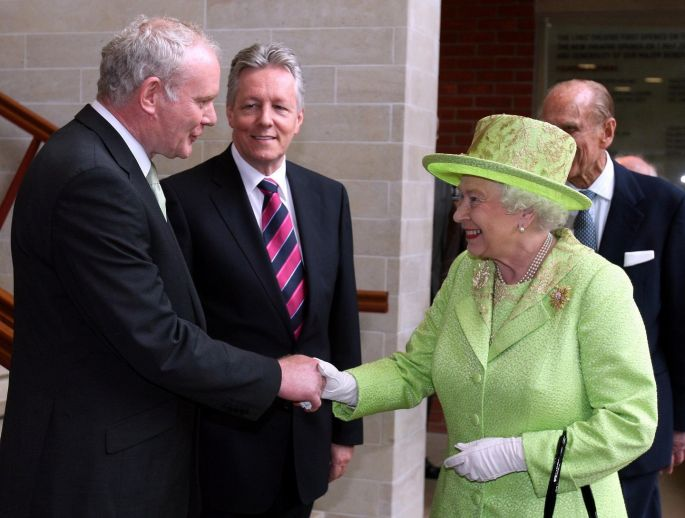 Queen Elizabeth II shakes hands with Northern Ireland Deputy First Minister Martin McGuinnesswatched by First minister Peter Robinson (centre) at the Lyric Theatre in Belfast. Photograph: PA