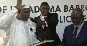 Adama Barrow (left) is sworn in as president of Gambia at Gambia's embassy in Dakar, Senegal. He was sworn into office in Senegal because Gambia's defeated long-time ruler Yahya Jammeh refuses to step down from power. Photograph: RTS via AP