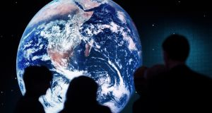 Reviewing globalisation: planet Earth  on a  screen behind participants of a panel session at the World Economic Forum,  in Davos, Switzerland. Photograph: Laurent Gillieron/EPA