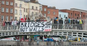 A Bridges Not Walls banner dropped from the Ha'Penny Bridge Dublin this morning (Friday 20th Jan) to coincide with protests over 3 continents in solidarity with people in the US. Photograph: Brenda Fitzsimons / The Irish times