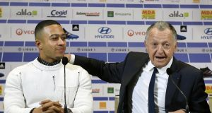 Memphis Depay listens as Lyon  president Jean-Michel Aulas speaks during a press conference to announce the signing of the Dutch forward from Manchester United. Photograph: Philippe Desmazes/AFP/Getty Images