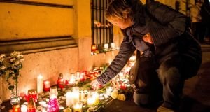 A mourner lights a candle to the memory of the victims of the school bus crash  in Italy. Photograph: EPA