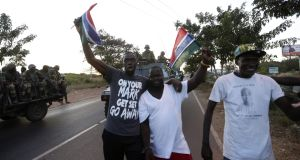 Supporters of President Adama Barrow cheer the Senegalese soldiers on patrol in Banjul, Gambia, on Sunday. Photograph: Legan Koula/EPA