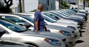 A man walks next to Chevrolet vehicles at a GM dealership in Miami, Florida: the Center for Automotive Research warns a tariff of 35 per cent could cut US car sales by 450,000 a year and cost 31,000 car industry-related jobs across the US. Photograph: Carlos Barria