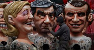 A man works with figures of presidential candidates Marine Le Pen, Francois Fillon  and Emmanuel Macron in Nice, southeastern France, during the preparation of the 133rd Nice Carnival. Photograph: Valery Hache/AFP/Getty Images