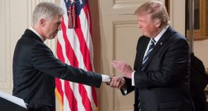 US president Donald J Trump shakes hands with Neil Gorsuch (left),  after announcing Gorsuch as his nominee for the Supreme Court in the East Room of the White House on Tuesday. Photograph: Michael Reynolds/EPA