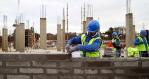 A construction worker lays a row of bricks on the Cairn Homes Marianella residential construction site in Dublin in November. Photograph: Chris Ratcliffe/Bloomberg