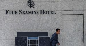 A member of staff outside the Four Seasons Hotel in Hong Kong from which Chinese billionaire Xiao Jianhua, founder of Beijing-based Tomorrow Group, was allegedly taken from his apartment by Chinese police. Photograph: Anthony Wallace/AFP/Getty Images.