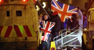 Loyalist protesters carrying Union flags clashing with police outside the City Hall in Belfast in 2012. Photograph: Paul Faith/PA Wire
