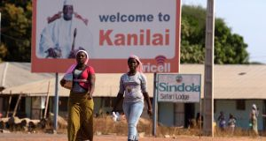 Women walk past a billboard bearing a picture of former Gambian leader Yahya Jammeh in his home town of Kanilai.  Photograph: Seyllouseyllou/AFP/Getty Images