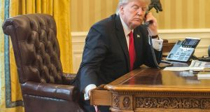 President Donald Trump inspects his desk as he speaks on the phone with King Salman of Saudi Arabia, in the Oval Office of the White House in Washington, Jan. 29, 2017. (Al Drago/The New York Times)