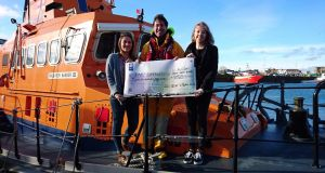 Howth RNLI station mechanic Ian Sheridan is presented with a cheque for €850 by DCU students Emily O'Carroll and Alice War from the Surf N Sail Club which raised the funds. Photograph: Rose Michael