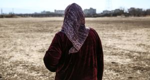 Syrian refugee Mona al-Shamali (52) looks out at the field where she now lives. Photograph: Sally Hayden