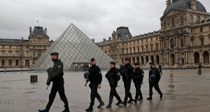 French police officers patrol  the courtyard of the Louvre museum after a soldier was attacked in Paris. Photograph: Christophe Ena/AP Photo