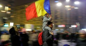 A child carries Romanian national flag during a demonstration in Bucharest, Romania, Sunday. Photograph: Vadim Ghirda/AP