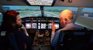 Simtech's  Bob Sheehan (right)  in a  flight simulator at  the company's Dublin Airport Logistics Park headquarters. Photograph; Dara Mac Dónaill
