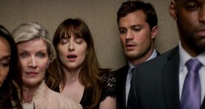 Dakota Johnson as Anastasia Steele and Jamie Dornan as Christian Grey in an elevator scene in Fifty Shades Darker