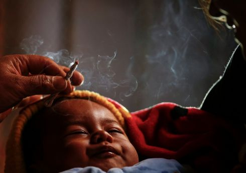 HEALING CEREMONY: A Nepalese shaman treats a baby during a healing ceremony in Kathmandu, Nepal. Photograph: Narendra Shrestha/EPA