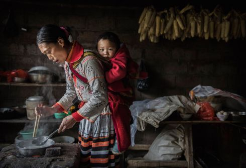 LUNAR NEW YEAR: A member of the Long Horn Miao ethnic minority group cooks after a Lunar New Year festival in Guizhou province, China. Photograph: Kevin Frayer/Getty Images