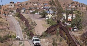 A US  border protection agent drives along a fence  separating the cities of Nogales, Arizona and Nogales, Mexico – a frequent crossing point for people entering the US illegally. Photograph: Scott Olson/Getty Images
