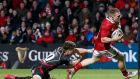 Munster's Andrew Conway on his way to scoring a try despite the  tackle from Dorian Jones of Dragons during the Guinness Pro 12 game at Musgrave Park. Photograph: Tommy Dickson/Inpho