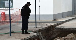 A policeman looks at the hole where an unexploded bomb dating from the second World War was found during work to expand a petrol station in Thessaloniki. Photograph: AFP/Getty Images