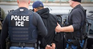 US Immigration and Customs Enforcement (ICE) officers detain a suspect as  part of an operation that involved hundreds of raids last week in at least six states. Photograph:  Charles Reed/US  Immigration and Customs Enforcement/Reuters