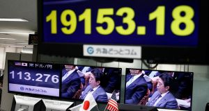 Japanese prime minister Shinzo Abe on a TV screen beside monitors showing the Japanese yen's exchange rate against the dollar