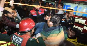 Pakistani policemen and volunteers move an injured  victim of a bomb attack in Lahore. Photograph: Arif Ali/AFP/Getty Images