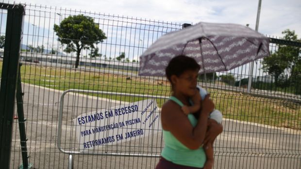 "A woman carries a baby in front of the Deodoro Sports Complex, which was used for the Rio 2016 Olympic Games, in Rio de Janeiro, Brazil, February 7th, 2017. The clapboard reads: "" We are in recess for maintenance of the pool, we will return in January. Merry Christmas and Happy new year"". Photo: Pilar Olivares/Reuters"