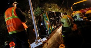 Rescuers gather around a   bus crash in Taipei, Taiwan, that left 32 passengers dead.  Photograph: Tyrone Siu/Reuters