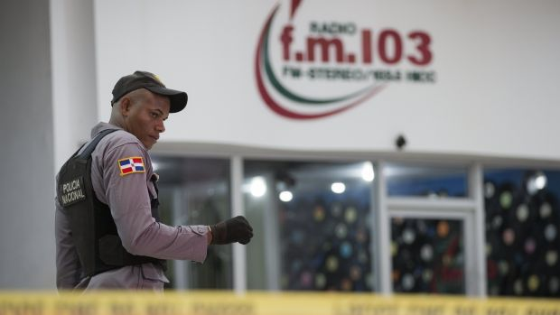 A Dominican policeman guards outside while investigations are going on at the facilities of the 103.5 radio station. Photograph: Orlando Barria/EPA
