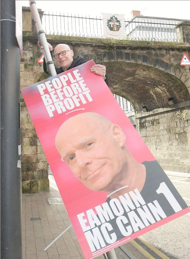 People Before Profit candidatae Eamonn McCann hangs a poster on Shipquay Street in Derry. Photograph: Trevor McBride
