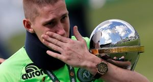 Jakson Follmann, a survivor of the LaMia airplane crash in Colombia, receives the Copa Sudamericana trophy in Arena Conda stadium before a charity match between Chapecoense and Palmeiras in Chapeco in January. Photograph: Leonardo Benassatto/Anadolu Agency/Getty Images