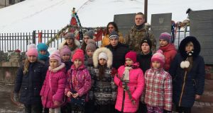 "The soldier posing with Tatyana and the children at a memorial to over  100 people killed during Ukraine's ""Revolution of Dignity"""