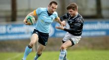 Garryowen's Ronan O'Halloran holds off a challenge from  Tom Fletcher of UCD Photograph: Ryan Byrne/Inpho.