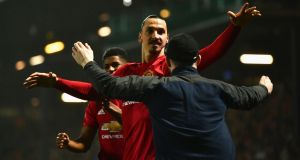Zlatan Ibrahmiovic celebrates with one of 7,000 travelling Manchester United fans after his late winner at Blackburn. Photograph: Dan Mullan/Getty