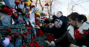 "People place flowers at the monument of the so-called ""Nebesna Sotnya"" (Heavenly Hundred),  anti-government protesters killed in Kiev in February 2014. Photograph: Valentyn Ogirenko/Reuters"