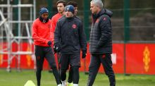 Jose Mourinho walks past Wayne Rooney during a Manchester United training session ahead of the  Europa League round-of-32 second leg against St Etienne. Photograph:  Jan Kruger/Getty Images