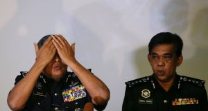 Royal Malaysian Police (RMP) Inspector-General of Police (IGP) Khalid Abu Bakar (left) demonstrates how a suspected assasin is believed to have poisioned  Kim Jong-nam. Photograph: EPA