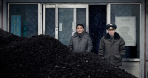 File photograph of North Koreans  and a pile of coal close to the border with China, viewed from the Chinese city of Dandong. China has banned coal imports from its neighbour. Wang Zhao/AFP/Getty