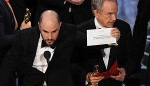 "'La La Land' producer Jordan Horowitz (L) shows the card reading Best Film 'Moonlight"" next to US actor Warren Beatty after the latter mistakingly read 'La La Land'. Photograph: Mark Ralston/AFP/Getty"