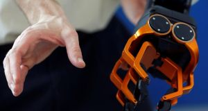 Handy friends or planning to take over? Olivier Stasse of CNRS tests the hand of Pyrene, a humanoid robot handyman. Photograph: Regis Duvignau/Reuters