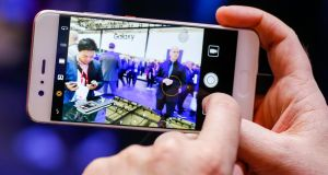 A P10 smartphone, manufactured by Huawei, is used to take a picture of the Samsung Electronics Galaxy Stand on the opening day of the Mobile World Congress. Photographer: Pau Barrena/Bloomberg