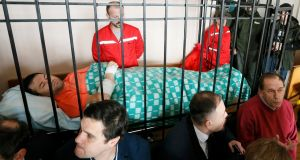 Roman Nasirov, head of Ukraine's powerful tax and customs agency, lies inside the defendant's cage during a court hearing in Kiev on Sunday. He claimed to have suffered heart problems when investigators raided his office. Photograph: Valentyn Ogirenko/Reuters