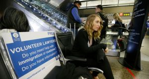 Asti Gallina, a volunteer law student from the University of Washington, sits at a station near where passengers arrive on international flights at Seattle-Tacoma International Airport. Photograph: Ted S Warren/AP Photo