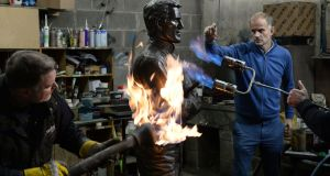 Sculptor Paul Ferriter (in blue) directs Ciaran Patterson  and Sandor Prsa putting the finishing touches to a bronze statue of AP McCoy. Photograph: Dara Mac Dónaill