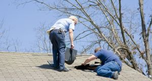Contractor repairing a damaged roof  after recent wind storms