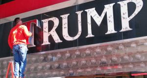 A worker removes letters from a Trump logo in Atlantic City, New Jersey. Photograph: Wayne Parry/AP