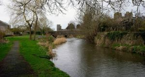 River walk by the Clashawley river at Fethard, Co. Tipperary, with Watergate Bridge and medieval town walls in the background